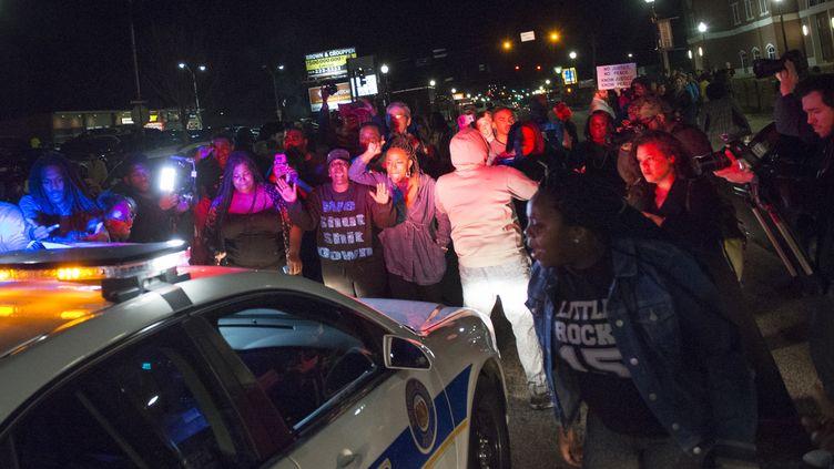 Des manifestants bloquent le passage d'un véhicule de police, le 11 mars 2015, à Ferguson (Missouri). (KATE MUNSCH / REUTERS)