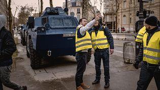 """Des """"gilets jaunes"""" prennent un selfie devant un véhicule blindé de la gendarmerie, à Paris, le 8 décembre 2018. (SIMON GUILLEMIN / HANS LUCAS / AFP)"""
