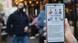 Un utilisateur de l'application TousAntiCovid dans une rue de Paris, le 23 octobre 2020. (JOAO LUIZ BULCAO / HANS LUCAS / AFP)