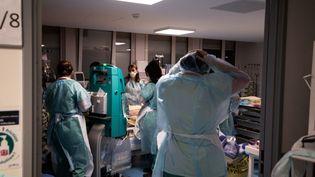 Des membres de l'équipe médicale d'un hôpital de Colombes (Hauts-de-Seine) traitent un patient atteint de Covid-19, le 5 mai 2021. (ALAIN JOCARD / AFP)