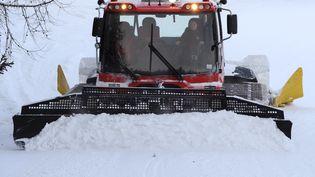 Une travailleuse saisonnière conduit une dameuse sur le domaine skiable de Sainte-Foy-Tarentaise, en Savoie, en février 2012. (JEAN-PIERRE CLATOT / AFP)