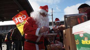Des militants de la CGT partagent un repas devant la gare de Fleury-les-Aubrais (Loiret), le 23 décembre 2019. (GUILLAUME SOUVANT / AFP)