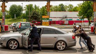 Un automobiliste en panne d'essence se fait aider pour amener sa voiture jusq'aux pompes à essence d'une station-service le 21 mai à Lille. (PHILIPPE HUGUEN / AFP)