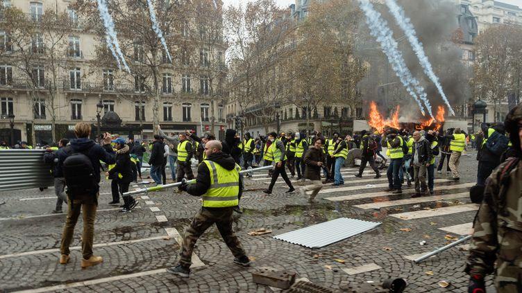 """Des """"gilets jaunes"""" lors de heurts avec les forces de l'ordre, samedi 24 novembre 2018 sur les Champs-Elysées. (BENOIT DURAND / HANS LUCAS / AFP)"""