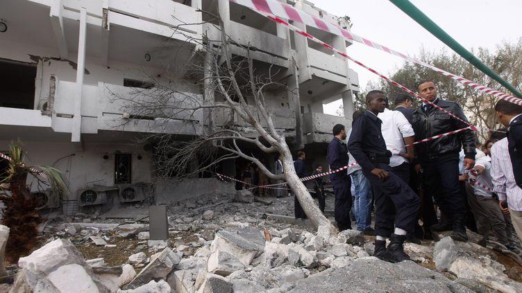 Des habitants de Tripoli (Libye) inspectent l'ambassade de France, attaquée par une voiture piégée le 23 avril 2013 au matin. (ISMAIL ZETOUNI / REUTERS)