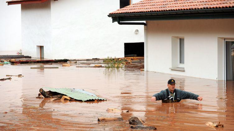 Un homme dans les rues inondées d'Ixtassou (Pyrénées-Atlantiques), le 4 juillet 2014. (GAIZKA IROZ / AFP)