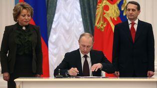 Le président russe Vladimir Poutine signe la loi rattachant la Crimée à la Fédération de Russie, vendredi 21 mars au Kremlin. (SERGEI CHIRIKOV / POOL / AFP)