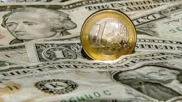 Une pièce d'un euro sur une pile de dollars. Photo prise le 13 mars 2015 àGodewaersvelde (France). (AFP PHOTO / PHILIPPE HUGUEN)