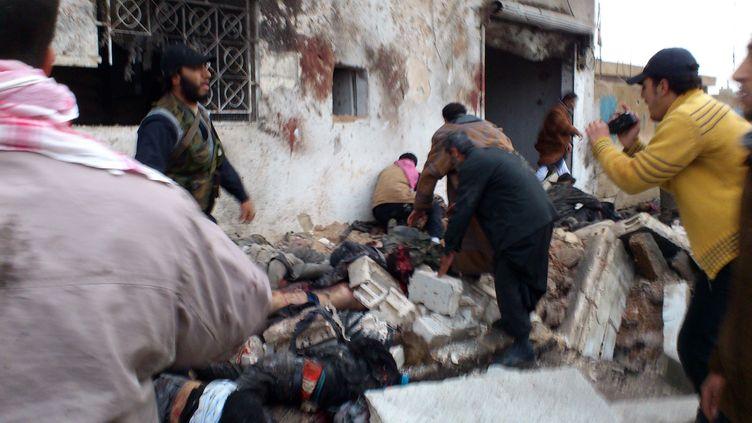 Photo transmise par l'opposition syrienne et présentée comme montrant des Syriens aidant les victimes d'un raid aérien devant une boulangerie à Halfaya (Syrie), le 23 décembre 2012. (AFP / SHAAM NEWS NETWORK)