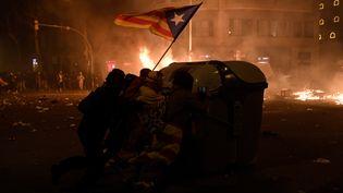Des manifestants indépendantistes catalans derrière une poubelle, le 18 octobre 2019, à Barcelone (Espagne), lors d'affrontements avec la police. (JOSEP LAGO / AFP)