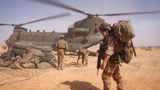 Des soldats françaisde la force Barkhane chargent un hélicoptère, au Burkina Faso, en avril 2021. (FRED MARIE / HANS LUCAS / AFP)