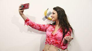 """Une jeune femme prend un selfie avec l'oeuvre """"The comedian"""" de Maurizio Cattelan, une simple banane scotchée au mur, à la foire d'art contemporain Art Basel de Miami, le 6 décembre 2019. (CINDY ORD / GETTY IMAGES)"""