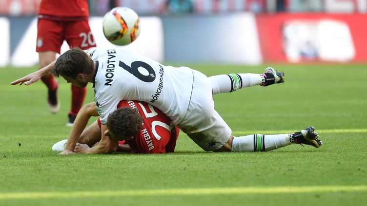 Harvard Nordveit (Borussia Moenchengladbach) se couche sur Thomas Müller (Bayern Munich) (CHRISTOF STACHE / AFP)