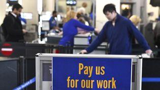 """Du personnel de l'aéroport de Philadephie (Etats-Unis) ont posé cette pancarte, """"payez-nous pour notre travail"""", le 25 janvier 2019. (MARK MAKELA / GETTY IMAGES NORTH AMERICA / AFP)"""