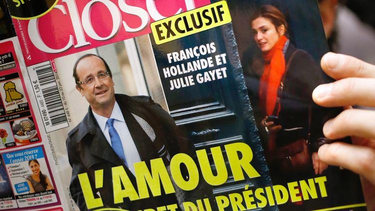 """Un homme lit le magazine """"Closer"""" du 10 janvier 2014 affirmant que François Hollande entretient une liaison avec l'actrice Julie Gayet. (THOMAS COEX / AFP)"""