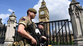 Un militaire patrouille aux côtés d'un policier a proximité du Parlement britannique, à Londres, le 24 mai 2017. (JUSTIN TALLIS / AFP)