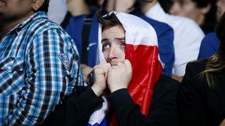 La détresse d'un supporter français qui assistait au match Espagne-France (2-0) depuis le Trocadéro, à Paris, où était installé un écran géant, le 23 juin 2012. (KENZO TRIBOUILLARD / AFP)