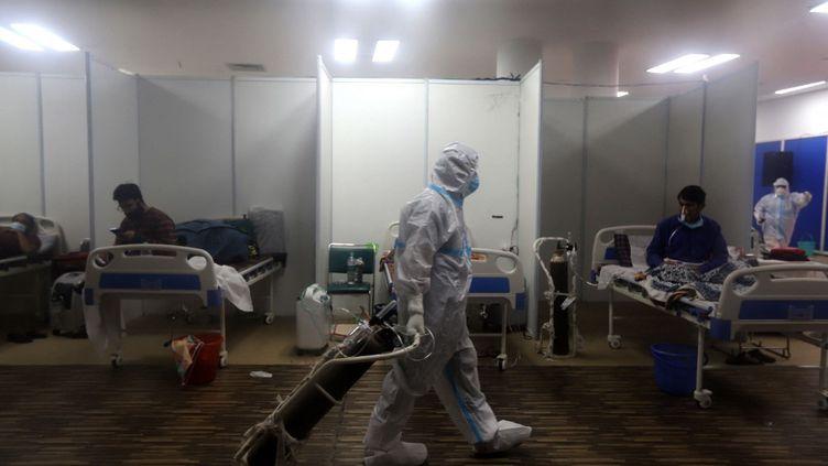 Un soignant s'occupe de patients atteints de Covid-19 dans un hôpital de New Delhi, en Inde, le 23 avril 2021. (AMARJEET KUMAR SINGH / ANADOLU AGENCY / AFP)