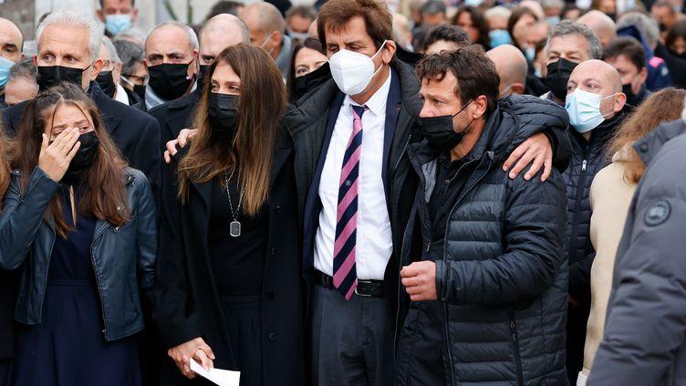 Max Guazzini, ancien président du Stade Français, enlasse de ses bras Loretta Denaro, veuve de Christophe Dominici, et Franck Comba, son ami de toujours lors des obsèques à Boulogne-Billancourt (THOMAS SAMSON / AFP)