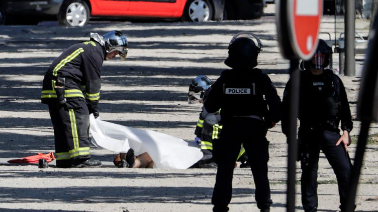 Le corps du suspect est recouvert par la police après l'attentat raté sur les Champs-Elysées, le 19 juin 2017. (THOMAS SAMSON / AFP)