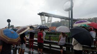 Des badauds regardent le viaduc Morandi,àGênes (Italie), après son effondrement, le 14 août 2018. (ANDREA LEONI / AFP)