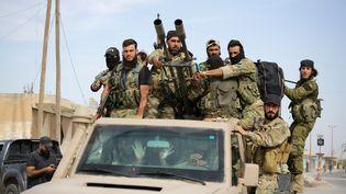 Des combattants syriens soutenus par la Turquie circulent dans la ville d'Ayn al-Arous (Syrie), le 14 octobre 2019. (BAKR ALKASEM / AFP)