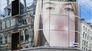 La façade du Monoprix s'est brusquement, soudainement, entre-temps parée d'un visage angélique qui porte les couleurs de la 12è biennale d'art contemporain  (BAC 2013)