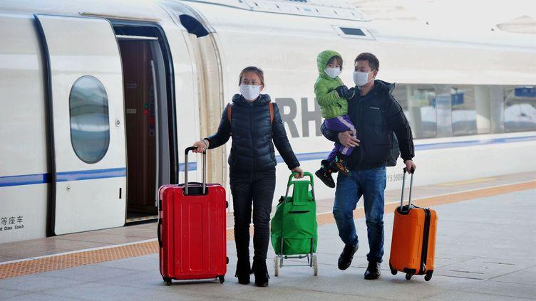 Une famille à la gare de Qingdao, dans l'est de la Chine, le 9 février 2020 (YU FANGPING / MAXPPP)
