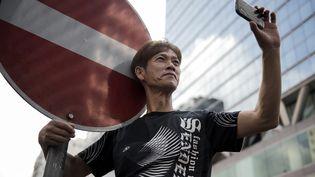Un homme prend une photo avec son téléphone dans le district de Kowloon, à Hong Kong, le 29 septembre 2014. (ALEX OGLE / AFP)