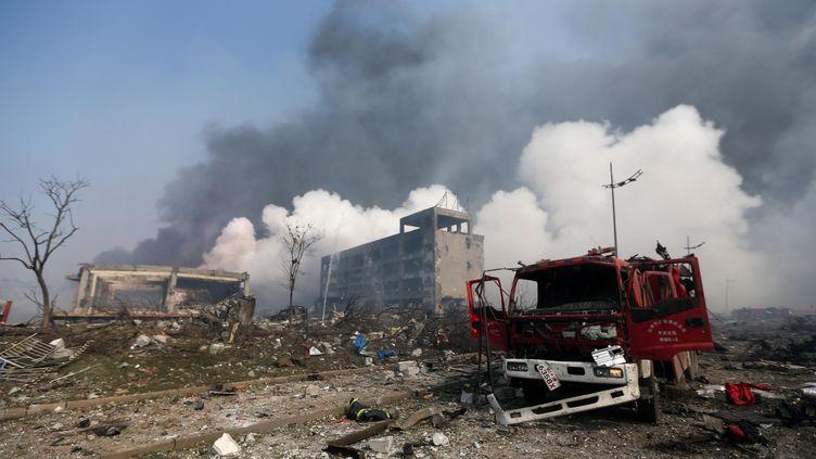 Un camion de pompiers endommagé sur le site des explosions survenues à Tianjin (Chine), le 13 août 2015. (STR / AFP)