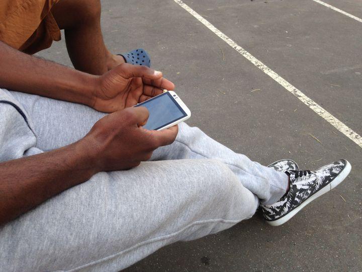 Ahmed Salem consulte son téléphone dans la cour du lycée désaffecté. (FLORIAN DELAFOI / FRANCETV INFO)