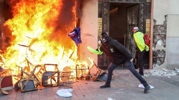 """Des manifestants ont incendié une boutique Longchamp à Paris lors de la 18e journée de mobilisation des """"gilets jaunes"""" le 16 mars 2019. (ZAKARIA ABDELKAFI / AFP)"""