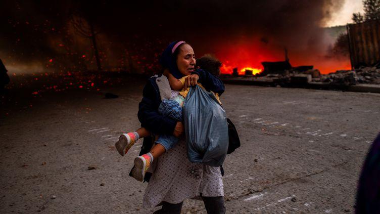 Une femme et son enfant fuient l'incendie du camp de migrants de la Moria, le 9 septembre 2020 à Lesbos (Grèce). (ANGELOS TZORTZINIS / AFP)