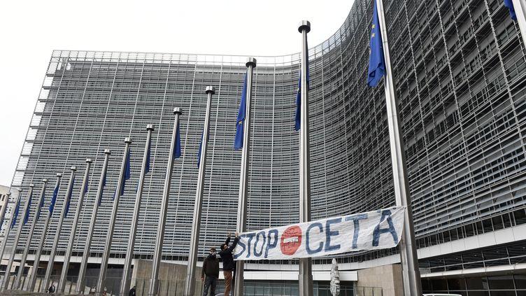 """Deux hommes installent une pancarte """"stop Ceta"""" devant les quartiers de la commission européenne à Bruxelles (Belgique), le 27 octobre 2016. (JOHN THYS / AFP)"""