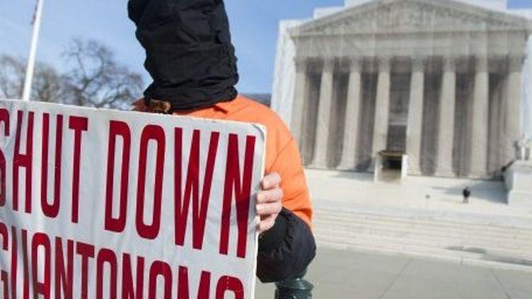Un manifestant en tenue orange, celle des prisonniers de Guantanamo, protestedevant la Cour suprême américaine, à Washington, le 8 Janvier 2013,contre la détention illégale de prisonniers dans le camp américain. (AFP PHOTO / SAUL LOEB)