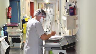 Un personnel soignant dans un couloir d'hôpital, le 1er avril 2020, à Aurillac. (J?R?MIE FULLERINGER / MAXPPP)