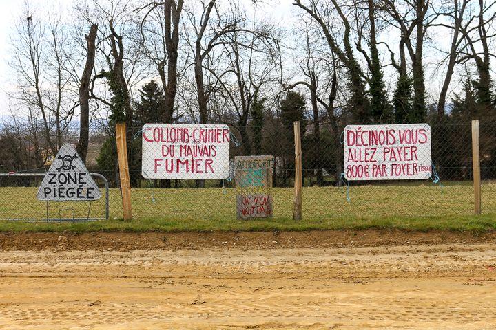 Le long de la future route construite sur son ancien champ, à Décines (Rhône),Philippe Layat a accroché des pancartes dénonçant le chantier. (BENOIT ZAGDOUN / FRANCETV INFO)