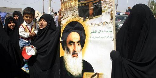 Femmes chiites tenant un portrait du grand aytollah Ali Sistani à Najaf (160 km au sud de Bagdad) le 14-4-2006. Ali Sistani est le dignitaire chiite le plus vénéré en Irak. (AFP - QASSEM ZEIN)