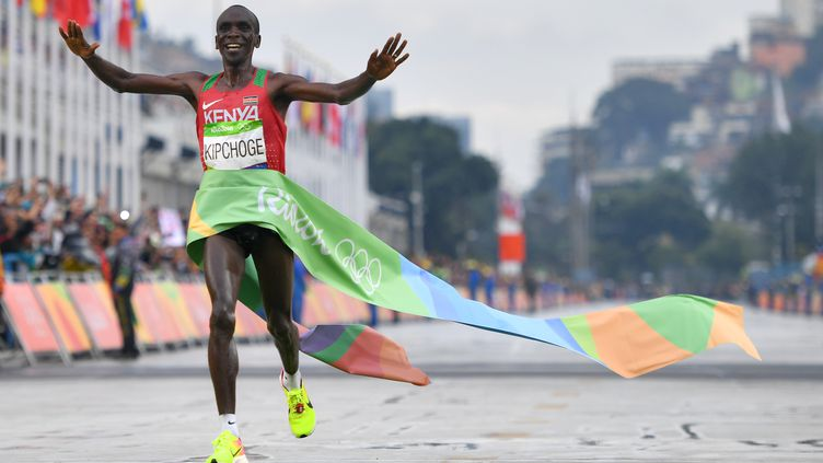 Le champion kenyanEliud Kipchoge franchit la ligne d'arrivée du marathon aux Jeux olympiques de Rio en vainqueur, le 21 août 2016. (OLIVIER MORIN / AFP)