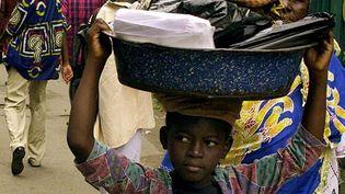Une jeune fille porte sur la tête les courses de son employeuse, le 30 août 2001, à Abidjan (Côte d'Ivoire). (Photo AFP/Georges Gobet)