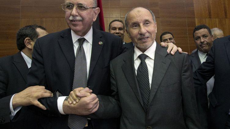 A gauche, le nouveau chef du gouvernement de transition libyen, Abdel Rahim al-Kib, félicité par le président du Conseil national de transition, Moustapha Abdeljalil, le 31 octobre 2011 à Tripoli.  (MARCO LONGARI / AFP)