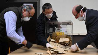 Des assesseurs dépouillent, équipés de masques pour se protéger du coronavirus, une urne lors du premier tour des municipales, le 15 mars 2020, à Strasbourg. (FREDERICK FLORIN / AFP)