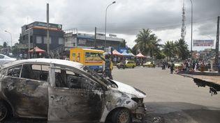 Voiture incendiée lors de manifestations contre un troisième mandat du président ivoirien Alassane Ouattara, dans le quartier de Cocody à Abidjan, la capitale économique de Côte d'Ivoire, le 19 octobre 2020. (SIA KAMBOU / AFP)