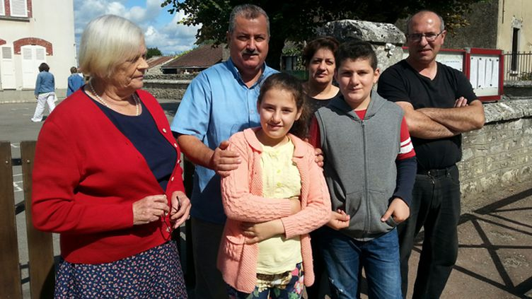 (A droite Pierre, qui accueille la famille (ici les deux parents et deux enfants) accompagnés d'une voisine © DR / Benjamin Illy)