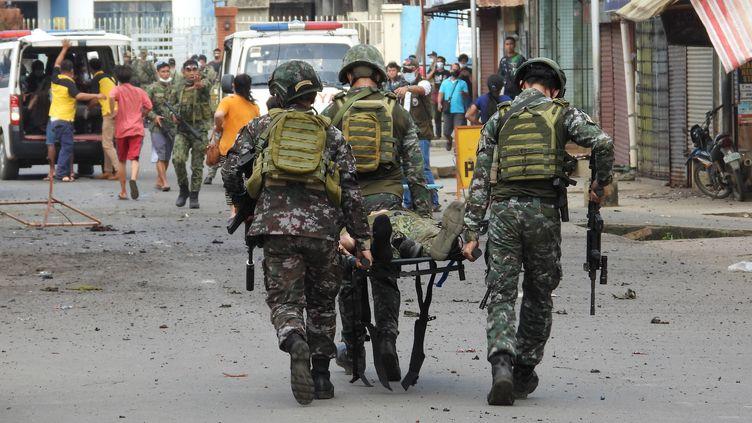 Des soldats évacuent un militaire blessé, après un double attentat survenu dans la ville de Jolo, aux Philippines, le 24 août 2020. (NICKEE BUTLANGAN / AFP)
