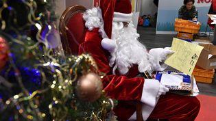 Un Père Noël lit une lettre à La Poste de Libourne (Gironde), le 20 décembre 2016. (GEORGES GOBET / AFP)