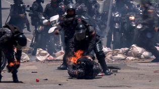 Un policier en feu secouru par un collègue, lors d'une émeute à Caracas (Venezuela) le 30 juillet 2017. (LEO RAMIREZ / AFPTV)
