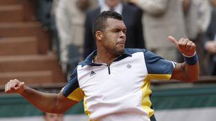 Jo-Wilfried Tsongaexécute sa célèbre danse des pouces après sa victoire contre le SerbeViktor Troicki, le 2 juin 2013 à Roland-Garros, à Paris. (ROMAIN TARLET / AFP)