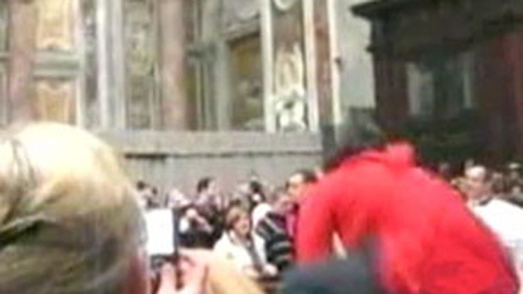 Maiolo (en rouge) saute une barrière en direction du pape en la basilique Saint-Pierre de Rome le 24 décembre 2009. (France 2)