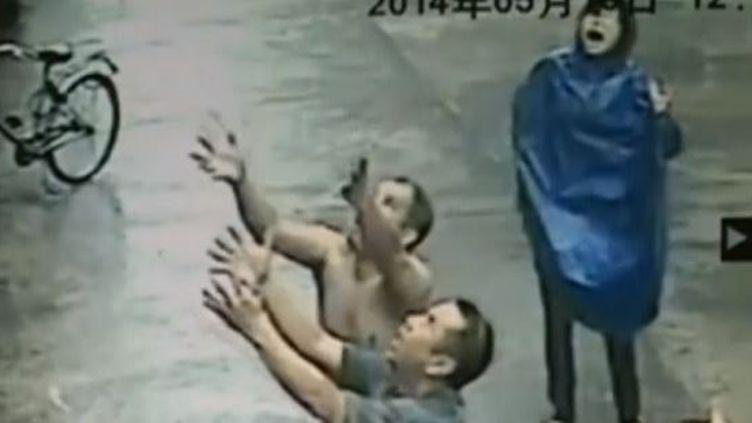 Un voisin s'apprête à rattraper un bébé tombé du 2e étage, à Xiaolan (Chine), le 18 mai 2014. (CCTV / REUTERS / FRANCETV INFO)